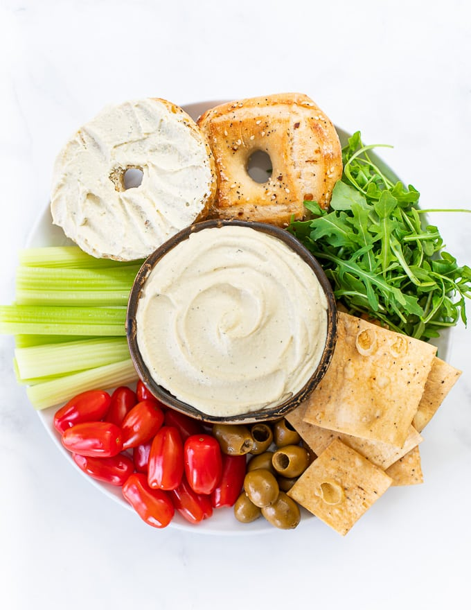 A vegan cream cheese platter with a bowl of vegan cream cheese, crackers, bagels and veggies