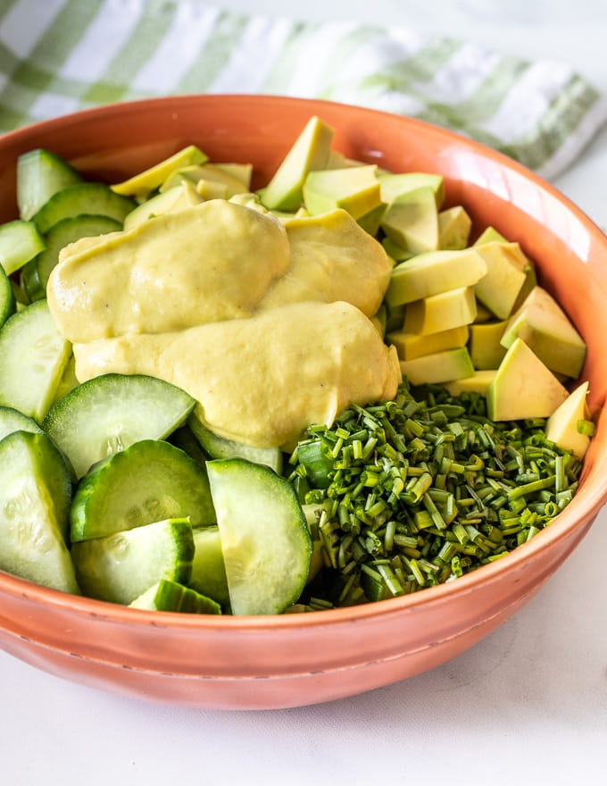 a salad with a dollop of avocado dressing on top