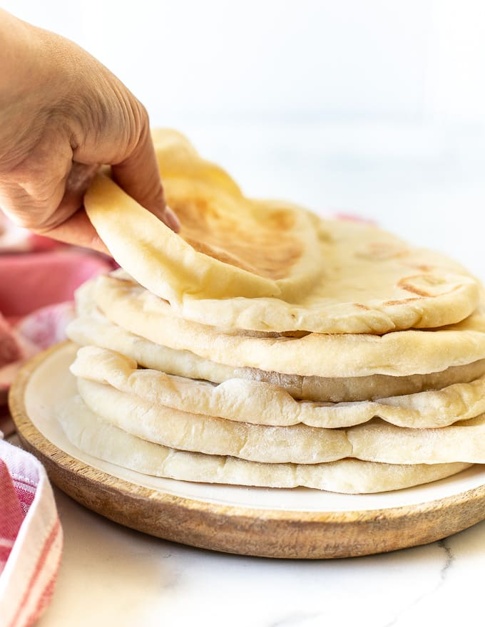 someone taking a flatbread from the top of a pile