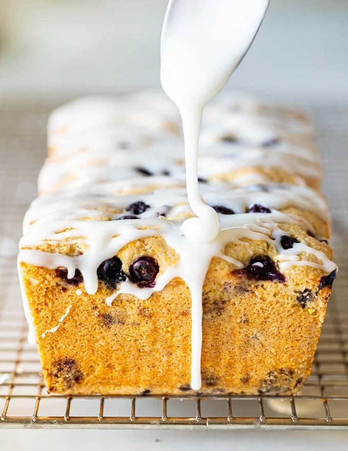 glaze being dribbled on a gluten-free lemon cake with blueberries