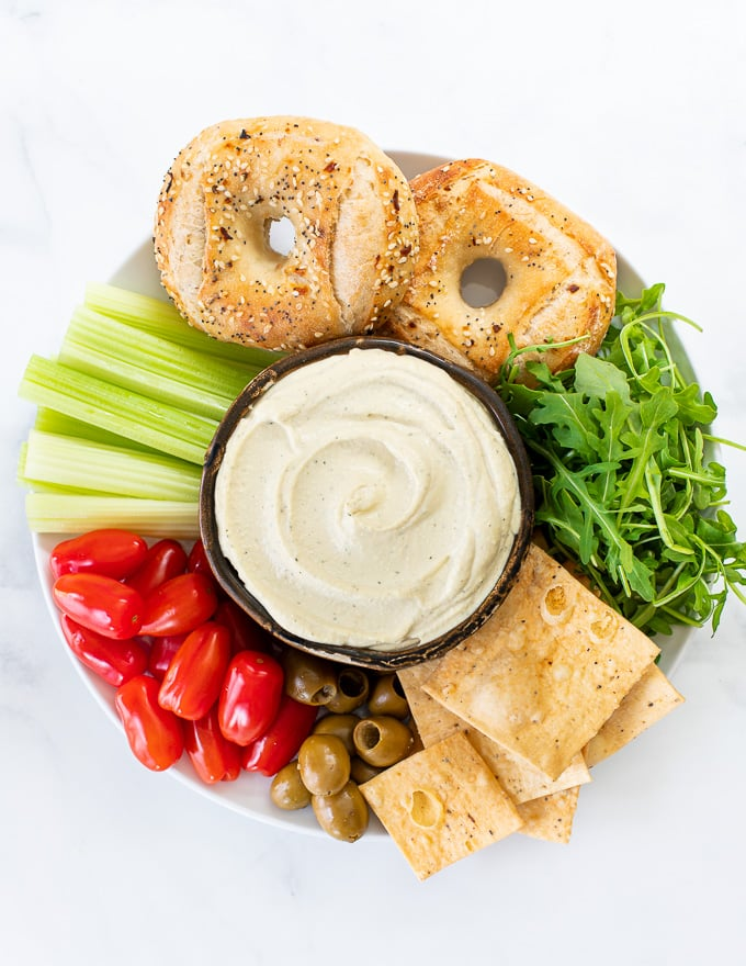 a bowl of vegan cream cheese surrounded by crackers, bagels and veggies