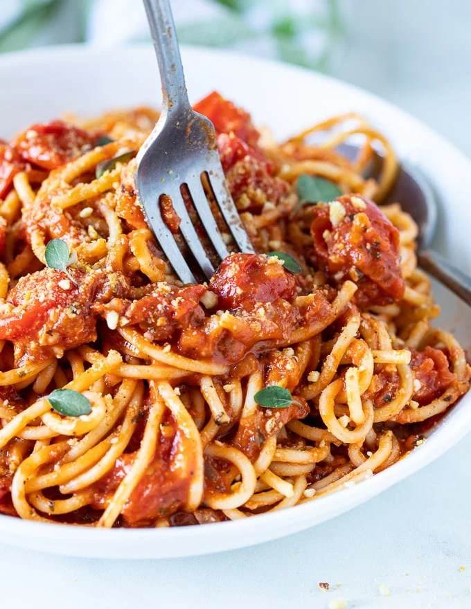 a fork about to dig into a bowl of spaghetti tossed in cherry tomato sauce