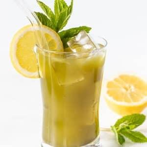 a glass of matcha lemonade garnished with a lemon slice and fresh mint