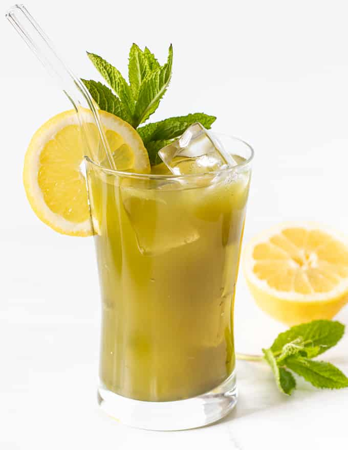 a glass of matcha lemonade garnished with a lemon slice and fresh mint