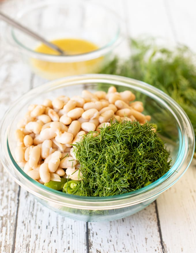 white beans, dill and sugar snap peas in a bowl