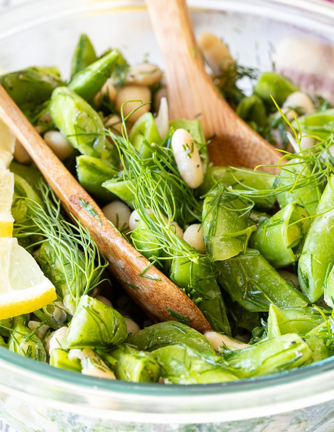 a close up shot of Sugar Snap Pea Salad being tossed in a bowl