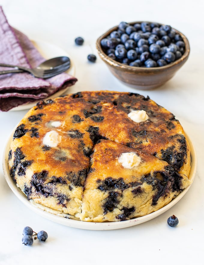 a giant, golden, blueberry vegan pancake on a plate with melted butter