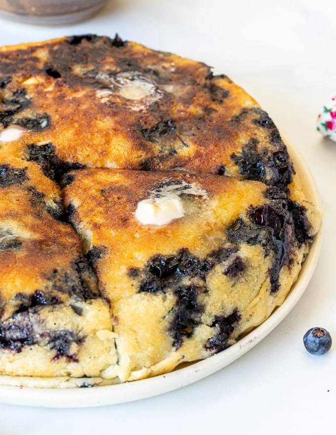 close up of giant blueberry vegan pancake with melted butter