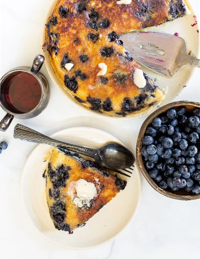 overhead photo of a giant blueberry vegan pancake with a slice on a plate, a bowl of blueberries and a jug of maple syrup