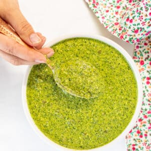 herby green sauce in a bowl with someone scooping out a spoonful. Photo taken from above.