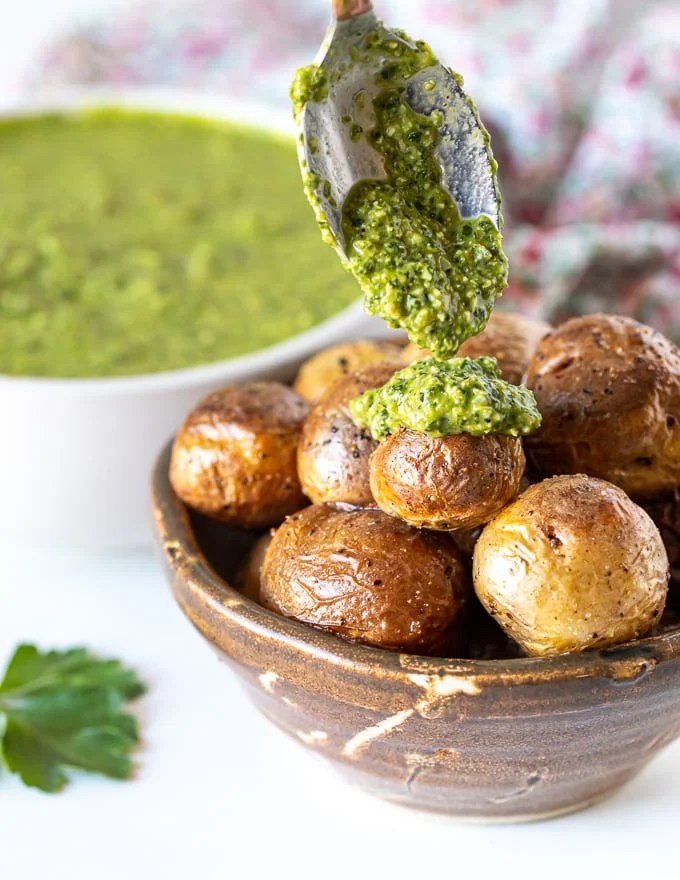 green sauce being dollopedon baby roasted potatoes