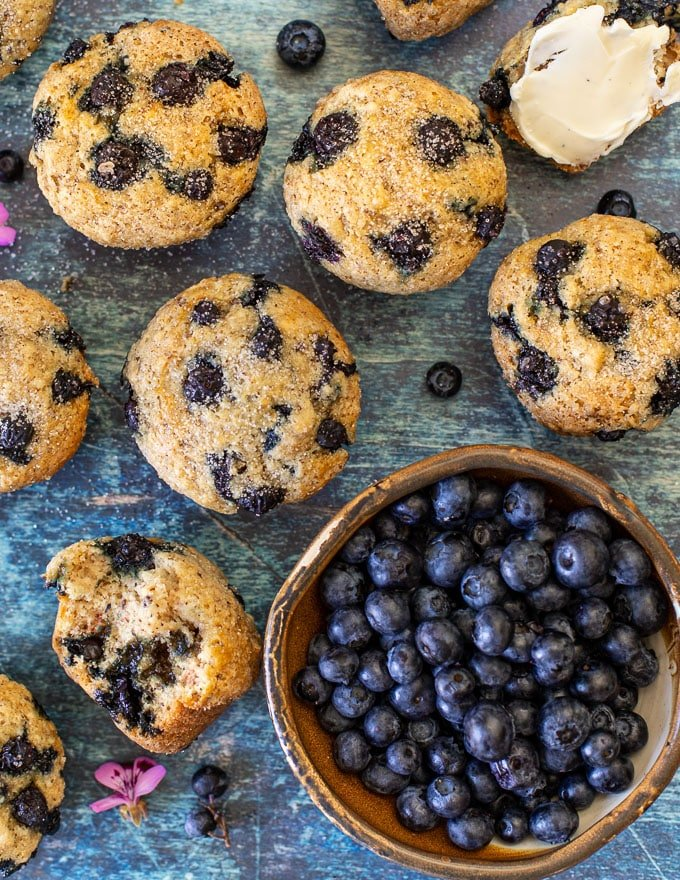 overhead shot of vegan blueberry muffins and a bowl of fresh blueberries