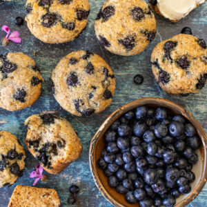 over head shot of a bowl of fresh blueberries and vegan blueberry muffins, a couple split and one buttered