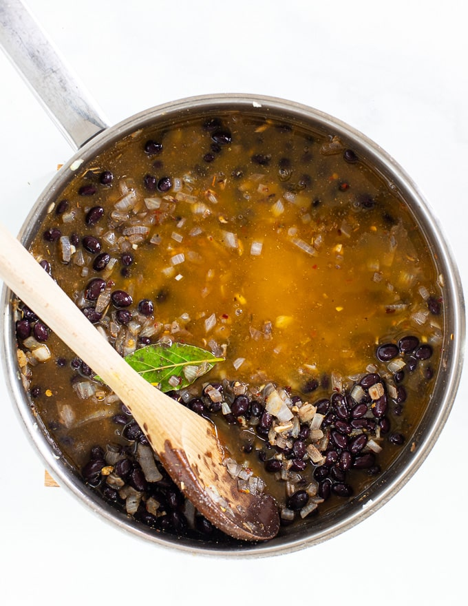 black beans cooking in a pan with stock for vegan meal prep