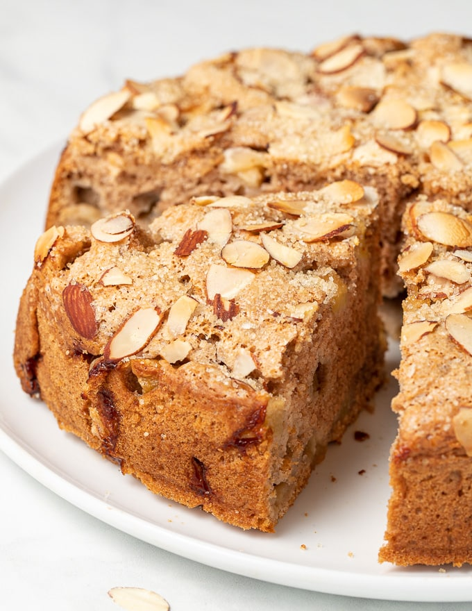 A slice of vegan apple cake with flaked almonds and coarse sugar on top