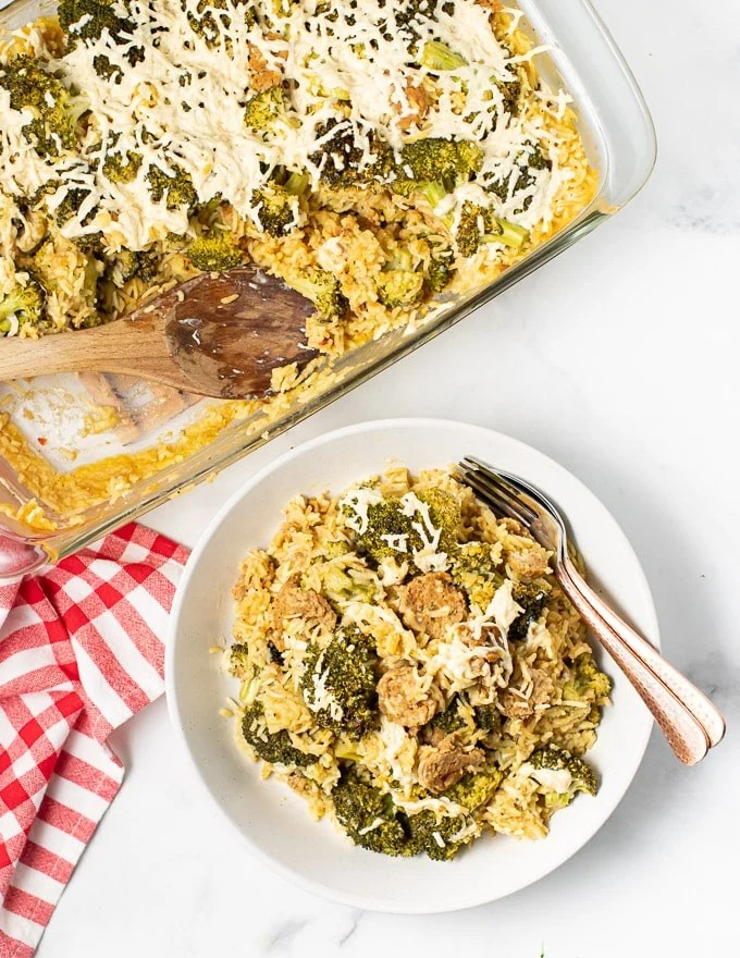 a dish of vegan broccoli rice casserole next to a bowl full with a fork and spoon on the side