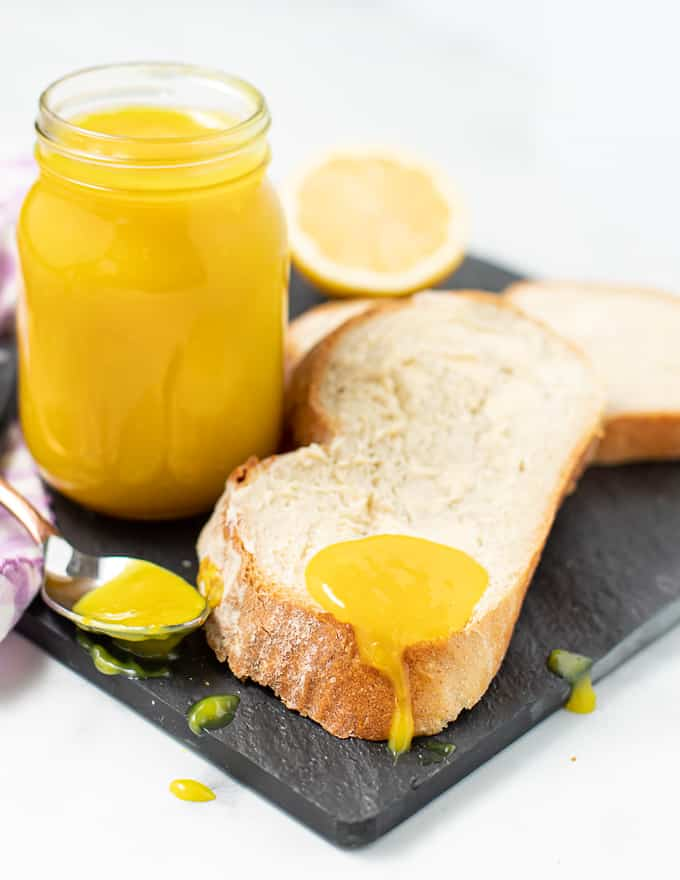 white bread with a spoon of vegan lemon curd dripping off it