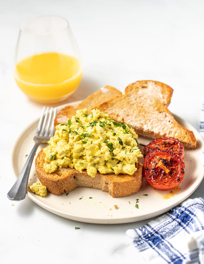 vegan scrambled egg on toast with a side of grilled tomatoes and more toast. A glass of orange juice in the background