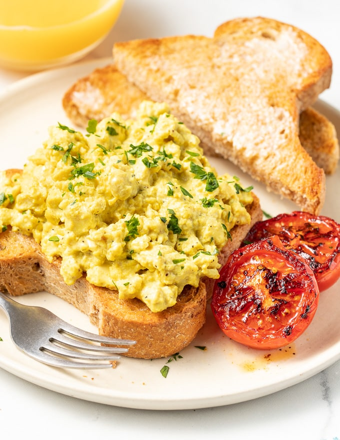 vegan scrambled eggs on toast with grilled tomato