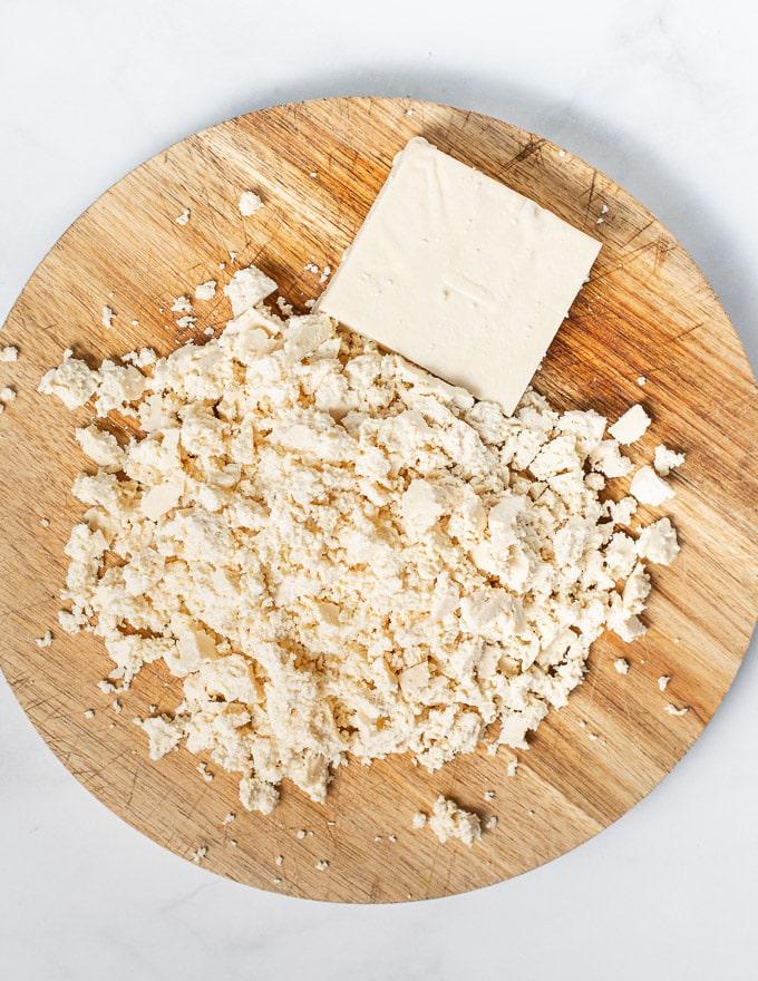 crumbled tofu on a wooden board, ready to make vegan scrambled eggs