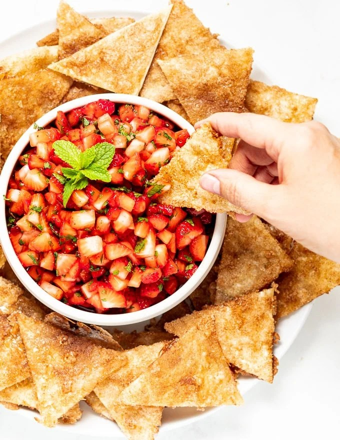 someone scooping up strawberry salsa on a homemade cinnamon chip