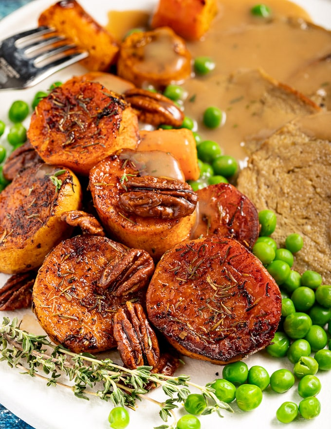 melting cinnamon roasted sweet potatoes on a plate with a roast dinner