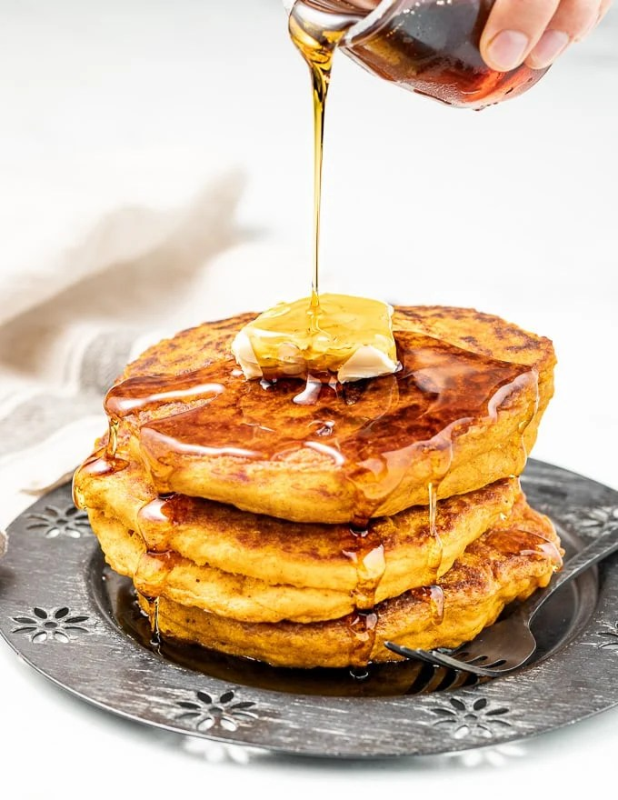 a stack of vegan pumpkin pancakes with a pat of butter and maple syrup being drizzled over from a small jar