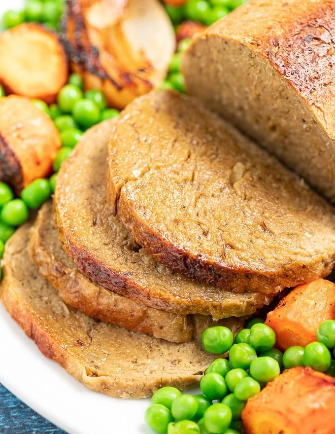 sliced vegan roast with vegetables