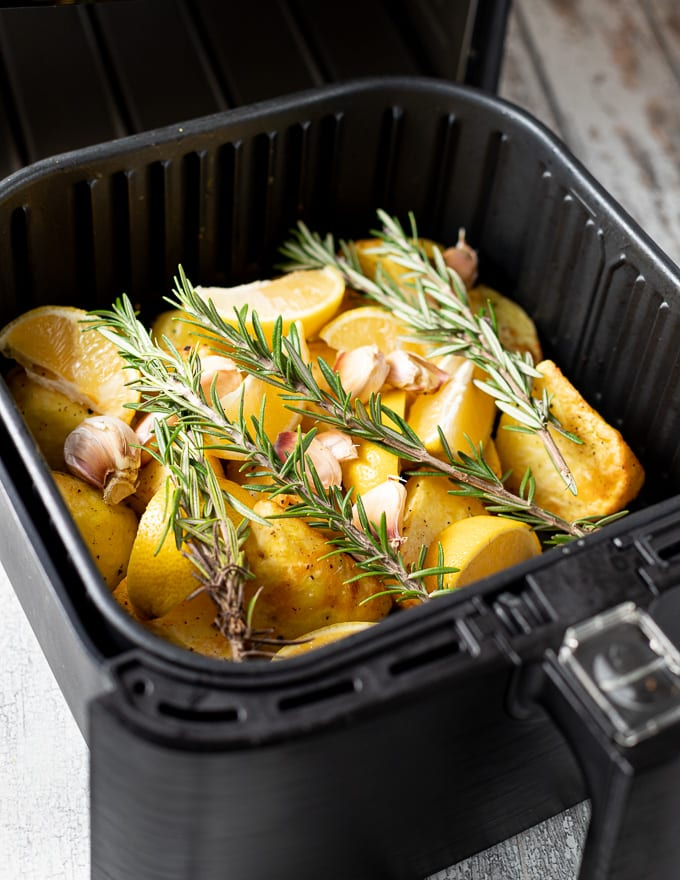 potatoes with lemon, garlic and rosemary in an air fryer basket