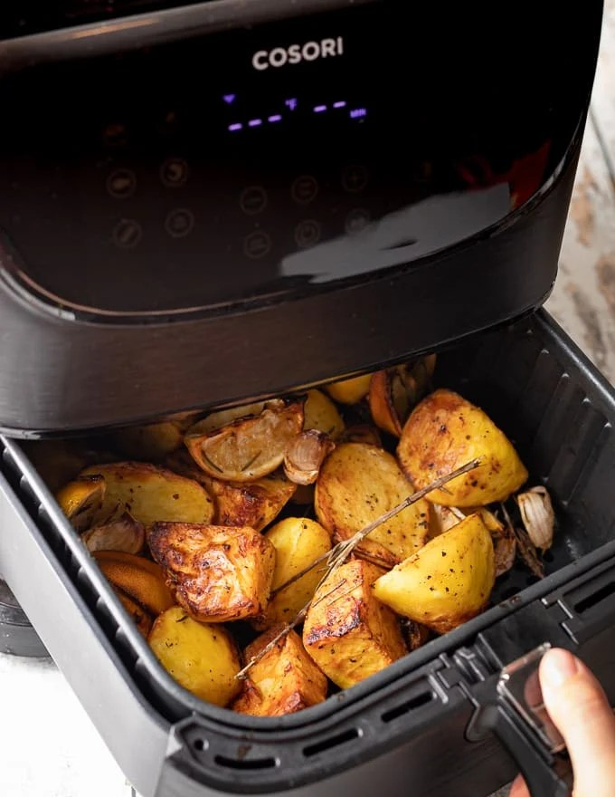 the basket of an air fryer being opened to show the potatoes inside