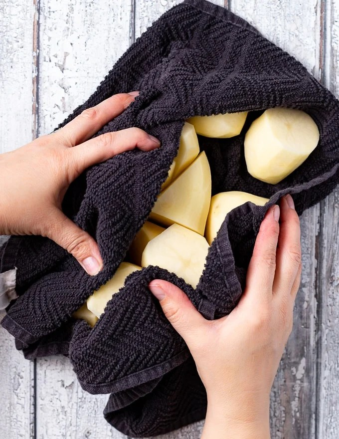 potato pieces being dried in a clean dish towel