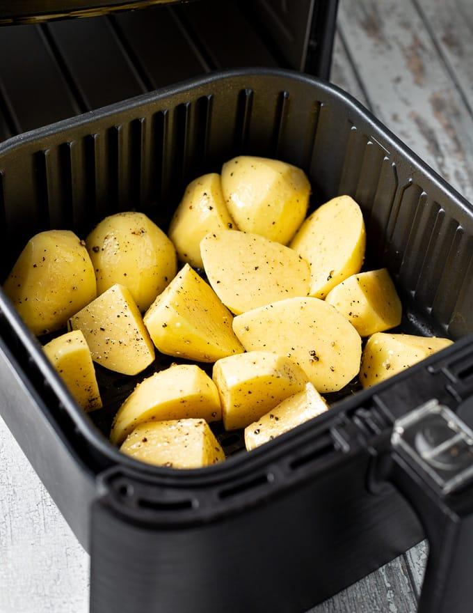 seasoned raw potatoes in the basket of an air fryer