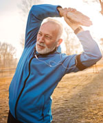 senior_man_stretching_in_park