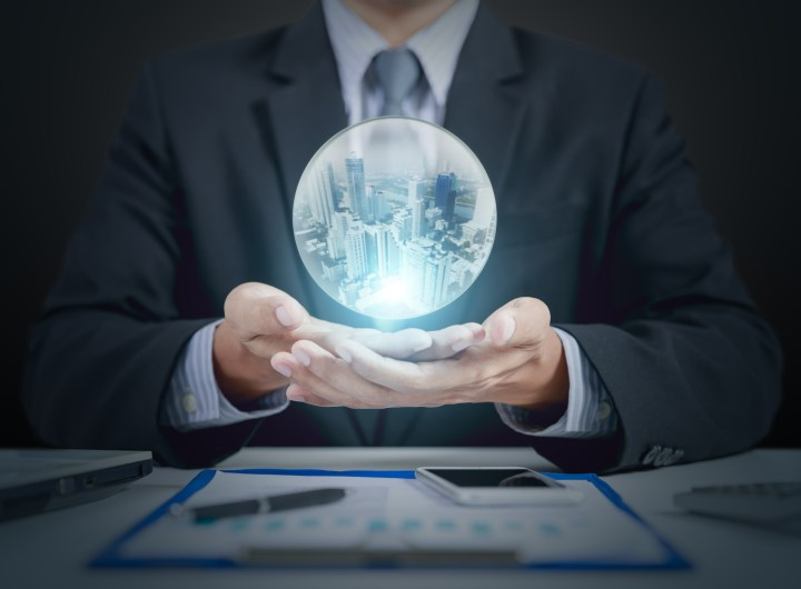 businessman hand hold crystal ball with building inside