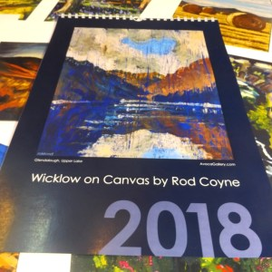 "2018 Calendar choice is Rod Coyne's ""Wicklow on Canvas"". Here we see the midnight blue cover resting upon twelve months of loose pages."