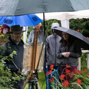 Workshop host, Rod Coyne, completes his painting demo for eager students. The umbrellas are up but spirits remain un-dampened.