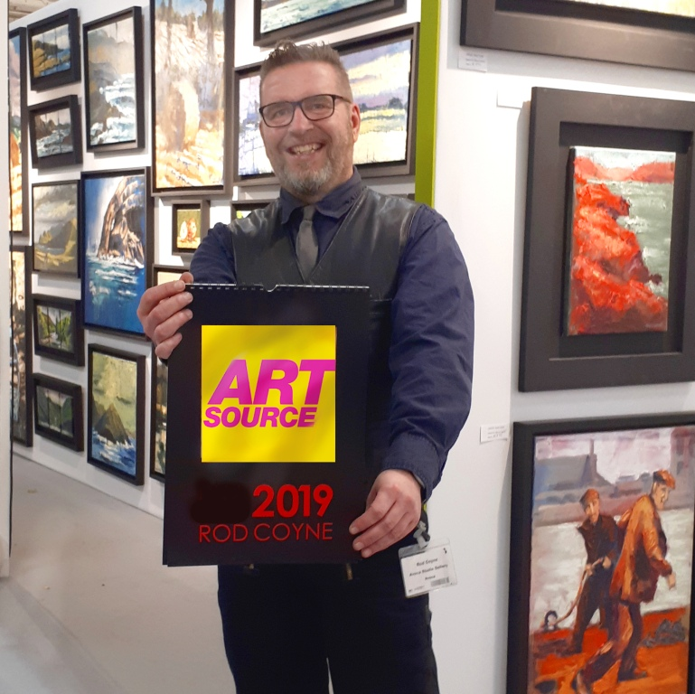 Rod Coyne photographed holding a sign for RDS in Art Source 2019