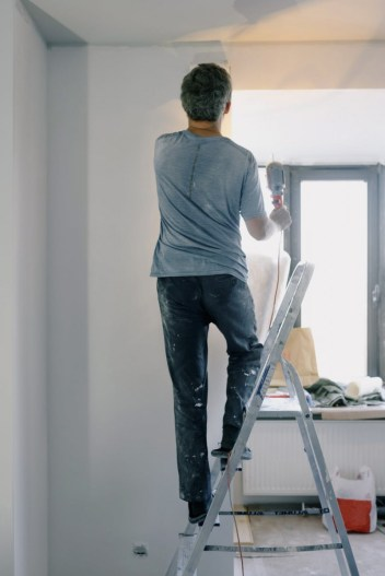 male builder with instrument in apartment