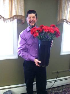 Dr. Nardi holding a full bucket of carnations ready to hand out on Valentine's Day!