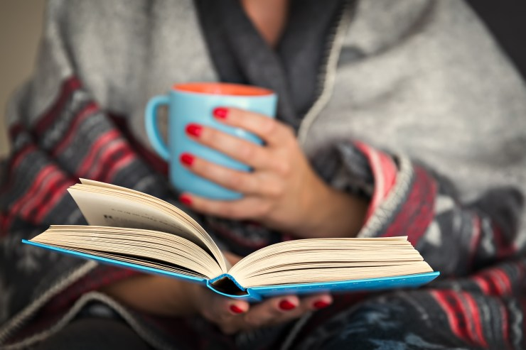 lady wrapped in shawl, cradling mug and reading a book