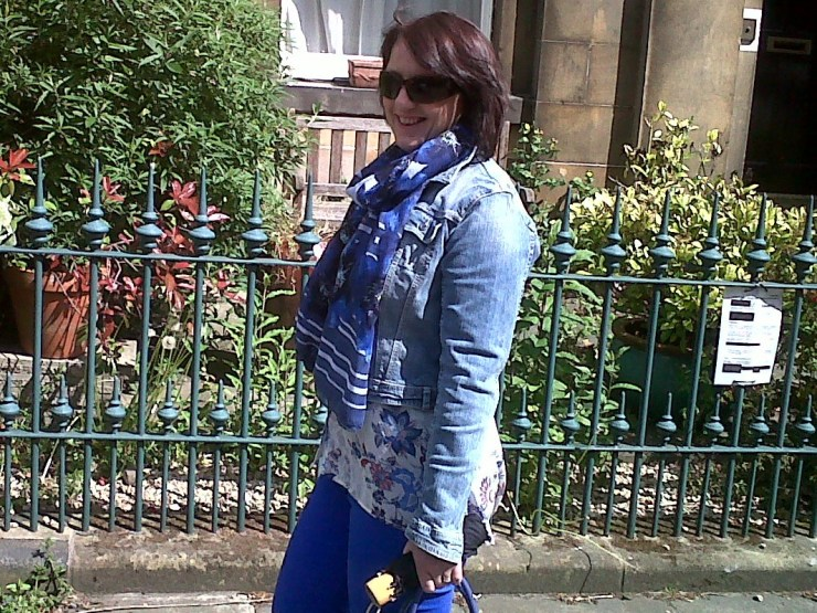 Style coach walking down the street, smiling, and wearing the denim jacket with contrasting scarf, and sunglasses