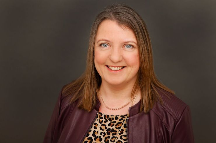 Professional headshot photo showing  Avril Dickson style coach smiling.  Style coach is wearing an animal print top and some gold jewellery under a wine coloured faux leather jacket.