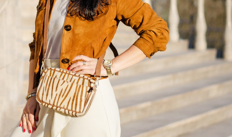 woman standing confidently wearing stylish clothes: a camel coloured cropped suede jacket with contrasting zebra print cross-body bag in gold and cream. Also wearing light cream/white top and wide leg trousers and has red nails