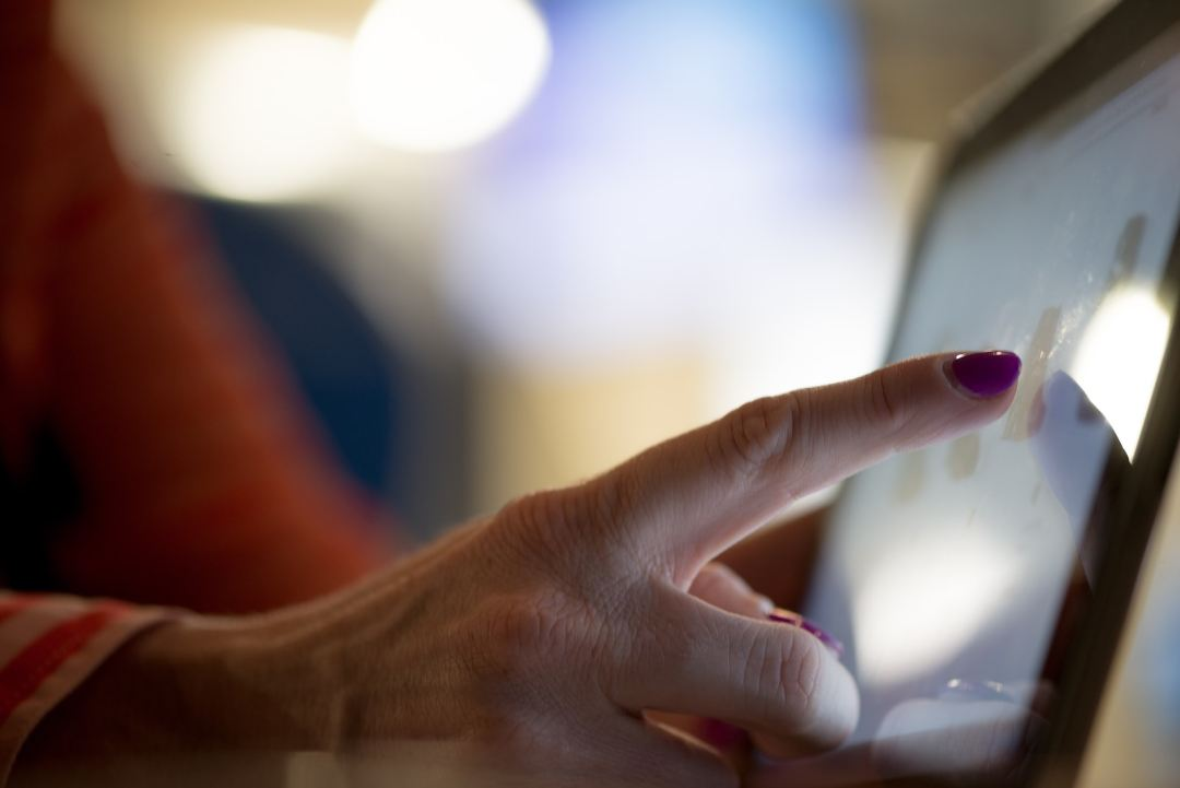 selective focus photography of person pointing at tablet computer