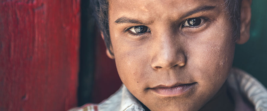 A Southeast Asian orphan looking into the camera with sad eyes