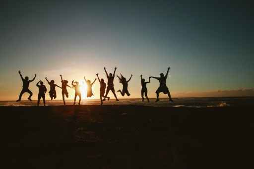 Silhouette of group of friends jumping at sunset.