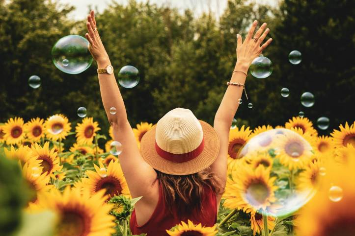 Woman wearing straw hat  surrounded by sunflowers and bubbles.