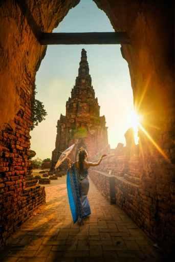 Woman dances among ancient ruins at sunset.