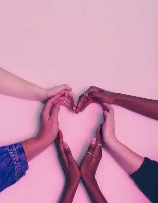 Diverse hands forming a heart shape.
