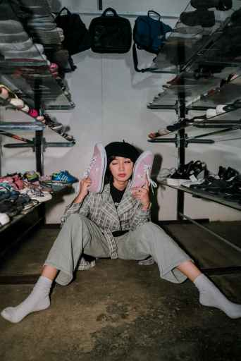 Woman sitting on closet floor with too many pairs of shoes to choose from.